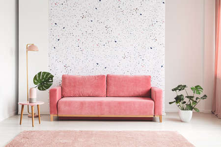 Foto de Pink couch between plant and lamp in bright living room interior with patterned wall. Real photo - Imagen libre de derechos