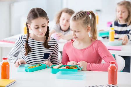 Photo for Two young girls during snack time in a school looking into each other's lunch boxes with healthy vegetables and bread. Bottles of fruit juices on the desk. Other kids in blurred background - Royalty Free Image