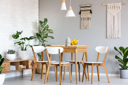 Photo pour Macrame hanging on gray wall above wooden table and chairs in bright dining room interior with lots of plants. Real photo - image libre de droit