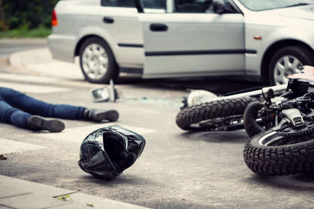 Photo pour Black helmet and motorcycle after dangerous traffic incident with car on the street - image libre de droit