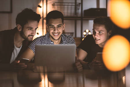Photo pour Group of smiling friends using laptop and uploading photos on social media - image libre de droit