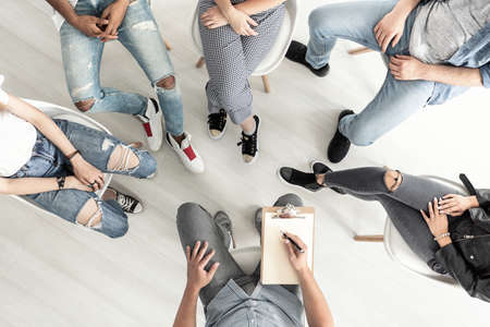 Foto de Top view of a group therapy session for teenagers struggling with depression - Imagen libre de derechos