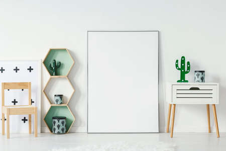 Photo pour Small cupboard with cactus shaped lamp and decorative box standing in white baby room interior with empty poster with place for your graphic, wooden chair and geometric shelves - image libre de droit