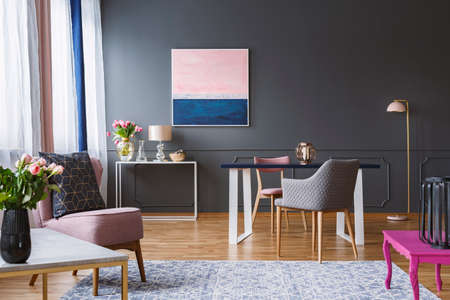 Foto de Pink and navy blue painting in grey living room interior with flowers and armchair. Real photo - Imagen libre de derechos