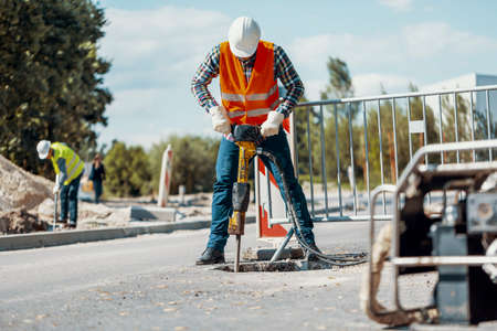 Photo pour Worker in reflective vest with drill repairing street during roadworks - image libre de droit