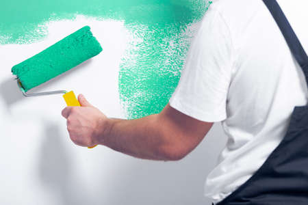 Photo for Close-up of worker with roller painting white wall on green - Royalty Free Image