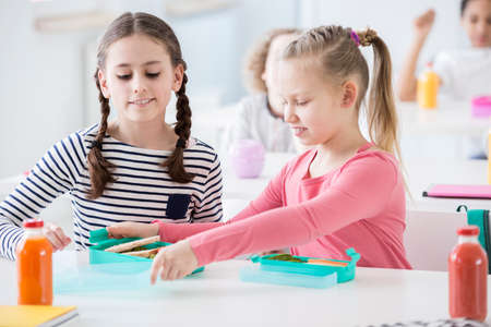 Foto per Girls eating healthy breakfast in the school canteen - Immagine Royalty Free
