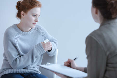 Photo pour Sad girl holding a tissue and talking to her therapist during a meeting - image libre de droit