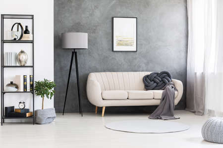 Photo for Poster mock-up on a gray, concrete wall and a leather beige settee in an industrial living room interior with black, wooden furniture - Royalty Free Image