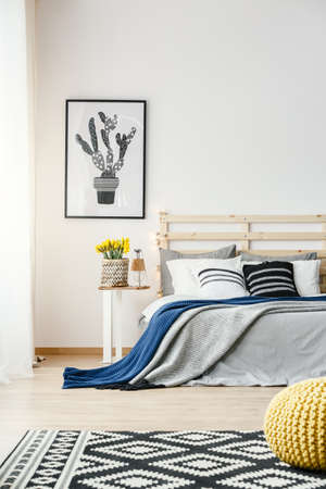 Foto de Black and white cactus poster hanging on the wall in bright bedroom interior with yellow fresh flowers, double bed and patterned carpet - Imagen libre de derechos