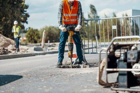 Photo pour Worker with a pneumatic hammer breaking asphalt at road construction site - image libre de droit