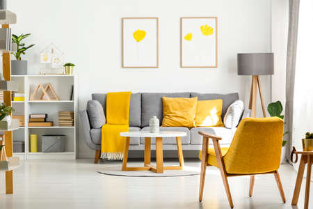 Photo pour Yellow wooden armchair and table in living room interior with posters above grey sofa. Real photo - image libre de droit