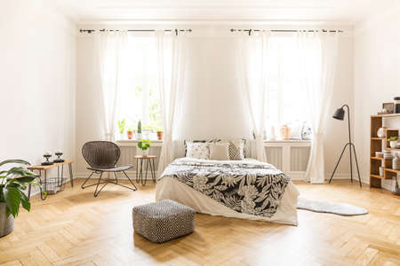 Photo pour Front view of a simple bedroom interior with a bed, pouf, windows and wooden floor - image libre de droit