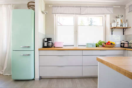 Photo for Neo mint fridge standing in real photo of bright kitchen interior with window, fresh fruits and pastel appliances placed on countertop - Royalty Free Image