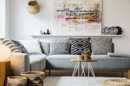 Foto de Real photo of a cozy couch with cushions standing behind a small table and in front of a shelf with a painting in boho living room interior with baskets and white rug - Imagen libre de derechos
