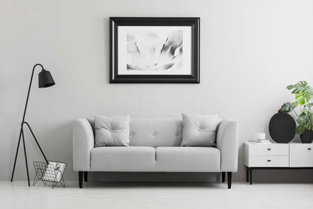 Foto de Framed photo on a wall above a fancy, gray sofa with cushions in a minimalist living room interior and place for a table. Real photo. - Imagen libre de derechos