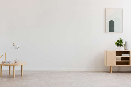 Photo pour Desk lamp on a small table and a simple, wooden cabinet in an empty living room interior with white wall and place for a sofa. Real photo. - image libre de droit