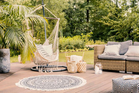 Foto de Pillows on hammock on terrace with round rug and rattan sofa in the garden. Real photo - Imagen libre de derechos