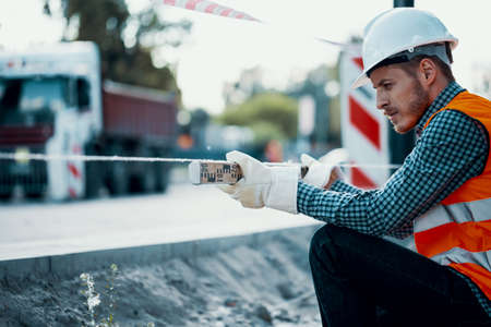 Foto per Worker measuring land with a leveling rod at a construction site - Immagine Royalty Free