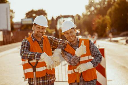 Foto de Two construction workers in hardhats and vests posing for a photo at the road - Imagen libre de derechos
