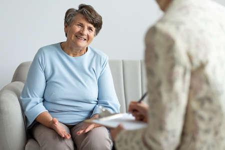 Foto de Elderly woman talking to a financial advisor about a loan during appointment - Imagen libre de derechos