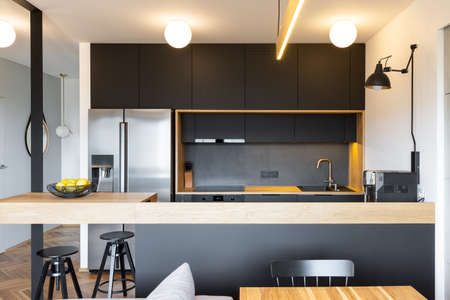 Foto de Black wooden furniture and an industrial lamp above a coffee machine in a beautiful, modern kitchen interior with dining space - Imagen libre de derechos