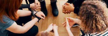 Foto de High angle view of hands of people in group therapy, talking and supporting each other - Imagen libre de derechos