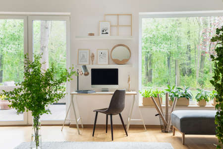 Photo pour Grey chair at desk with desktop computer in scandi open space interior with windows. Real photo - image libre de droit