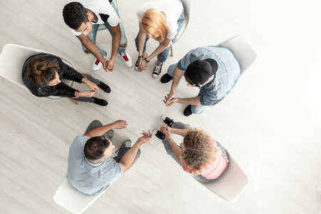 Foto de Top view on group of teenagers sitting in a circle during consultation with counselor - Imagen libre de derechos
