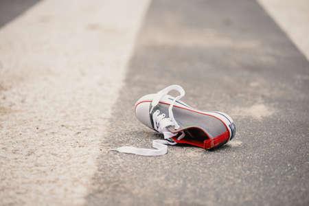 Photo pour Child's shoe on the street after dangerous traffic incident - image libre de droit