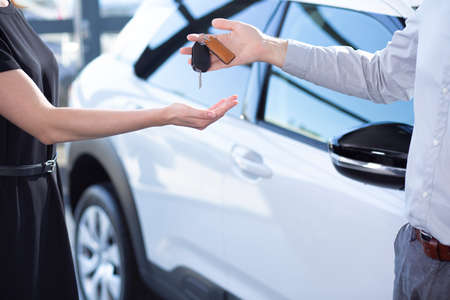 Photo pour Close-up of seller's hands with keys and buyer after transaction in car showroom - image libre de droit