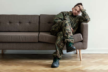 Foto de Helpless soldier sitting on a couch while waiting for a therapy session - Imagen libre de derechos