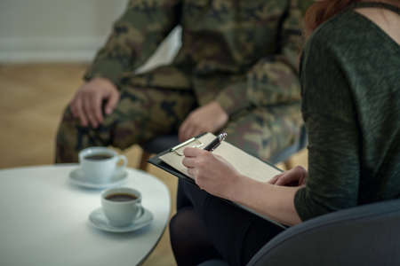 Foto de Close-up of psychologist writing down notes while talking to her patient from army - Imagen libre de derechos