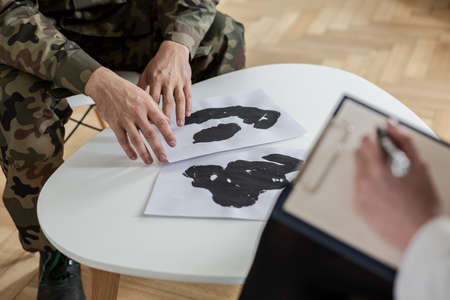Foto de Close-up of soldier's hands touching papers with ink stains during a therapy - Imagen libre de derechos