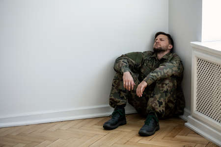 Foto de Depressed army man in uniform sitting in a corner of an empty room. Place for your poster on the wall - Imagen libre de derechos