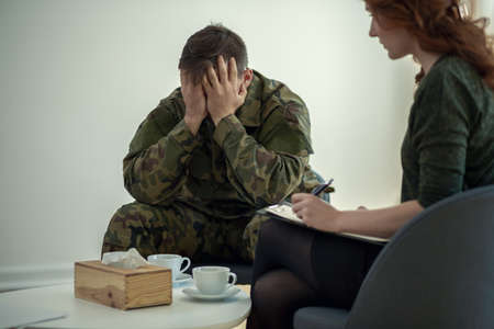 Foto de Soldier hiding his face in his hands while talking to a psychiatrist during therapy - Imagen libre de derechos