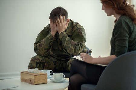 Foto de Soldier hiding his face in his hands while talking to a psychiatrist during therapy - Imagen libre de derechos