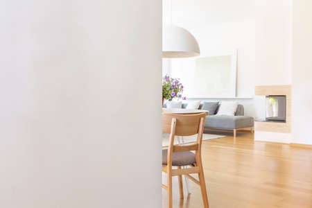 Photo pour White empty wall with copy space in living room interior with chair and wooden floor. Real photo with a place for your light switch - image libre de droit