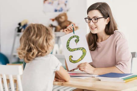 Foto de A child with development problems with a professional speech therapist during a meeting. Tutor holding a prop poster of a snake as a letter 's'. - Imagen libre de derechos