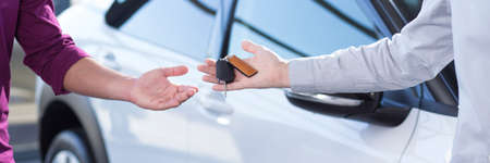 Photo for Panorama and close-up of car seller's hand with keys and buyer's hand after transaction - Royalty Free Image