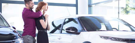 Photo pour Panorama of husband making surprise to wife in a car showroom - image libre de droit
