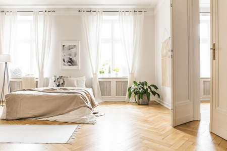 Photo pour Spacious and bright bedroom interior with beige decorations, hardwood floor and a book on the window sill seat - image libre de droit