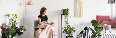 Foto de Young woman covered with blanket sitting on armchair and reading a book in white apartment interior with many fresh plants - Imagen libre de derechos