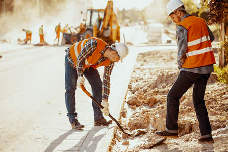 Photo pour Workers in reflective vests using shovels during carriageway work - image libre de droit