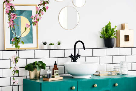 Foto de Close-up of a flower, graphic on the wall and wash basin on a turquoise cupboard. Real photo - Imagen libre de derechos