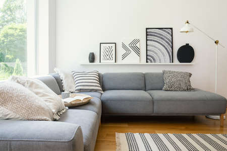 Photo pour Real photo of white Scandi sitting room interior with metal lamp, corner sofa with cushions and modern art posters - image libre de droit