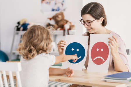 Foto de Young kid pointing at graphic with a smiley face during a psychotherapy session - Imagen libre de derechos