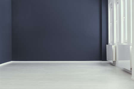 Foto de Empty minimal navy blue living room interior with copy space and grey floor. Real photo. Place for your sofa - Imagen libre de derechos