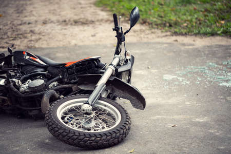 Photo pour Broken motorcycle on the road after traffic incident - image libre de droit