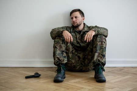 Foto de Tired professional soldier in green uniform sitting on the floor next to a gun - Imagen libre de derechos